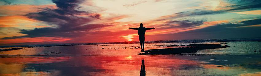 A person standing on a frozen lake in front of a multicolored sunset. The colors are pink, purple, yellow, and blue.