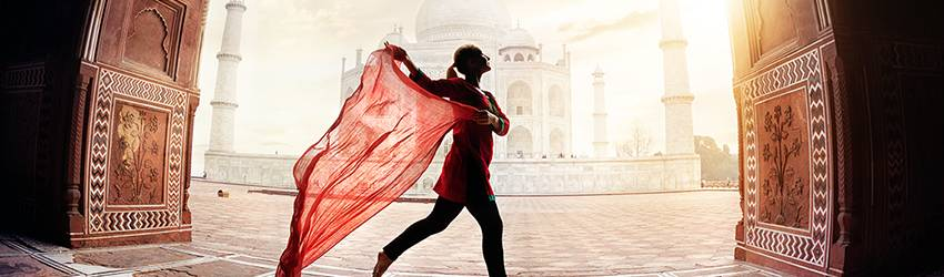 A woman dances with a red scarf in front of the Taj Mahal.