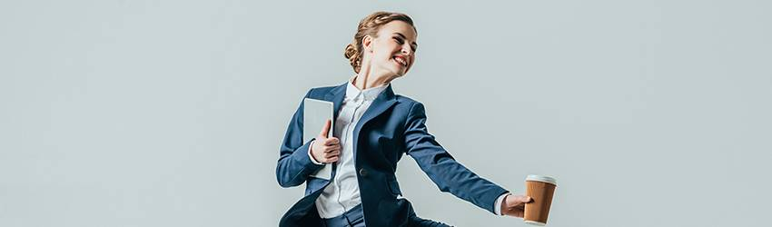 A woman jumps into the air with motivation. She is dressed for business because it is Capricorn season.