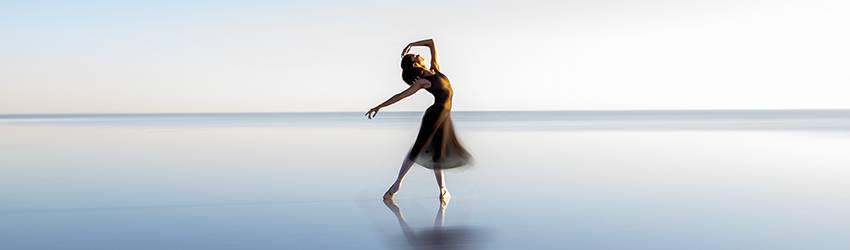 A woman dances in the ocean in a purple flowing dress.