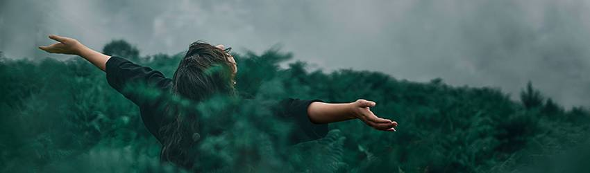 A woman holds her arms open in a green forest. She is opening herself to affirmational abundance in Virgo season.