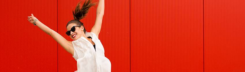 A woman jumps energetically in the air in front of a red feature wall.