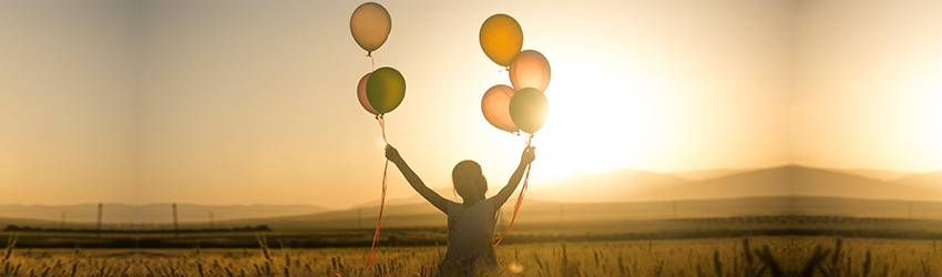 A girl holding balloons in both hands and running off into the sunset.