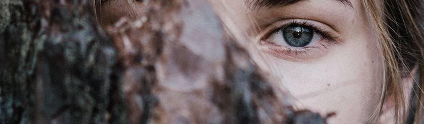 A blue eyed woman hides her eye behind a black piece of cloth.