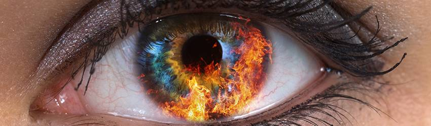 A close up of an eye with fire in the iris. This represents Aries, a fire sign.
