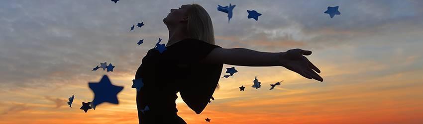 Woman dances under a starry sky.