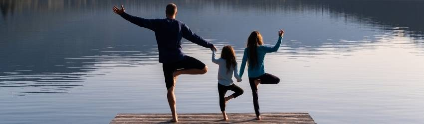 Three people stand on a pier in tree pose. They are holding hands.