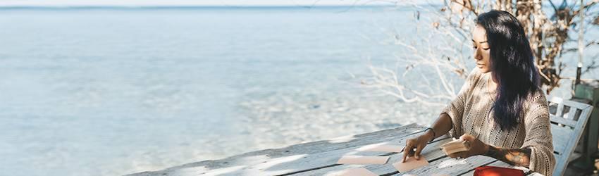 A woman doing a Tarot reading on a beach.