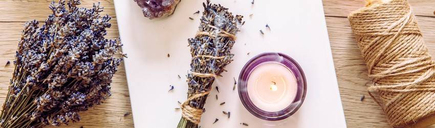 A New Moon ritual is set out on a wooden table. There are lavender bundles, white candles, and amethyst crystals on a white tile.