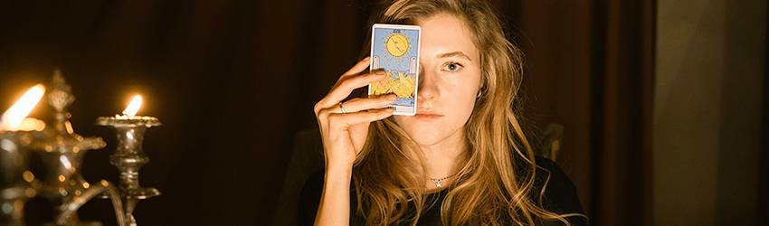 A woman holds The Sun Tarot card in front of her eye as she sits in a darkened room lit by candles.