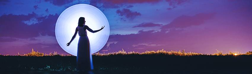 A woman standing in front of the Full Moon.
