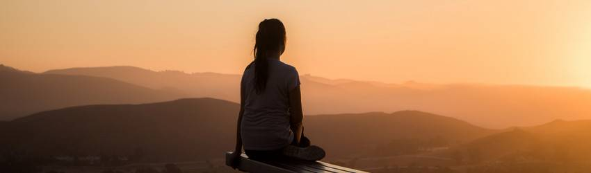 A person sits and reflects while watching an orange sunset.