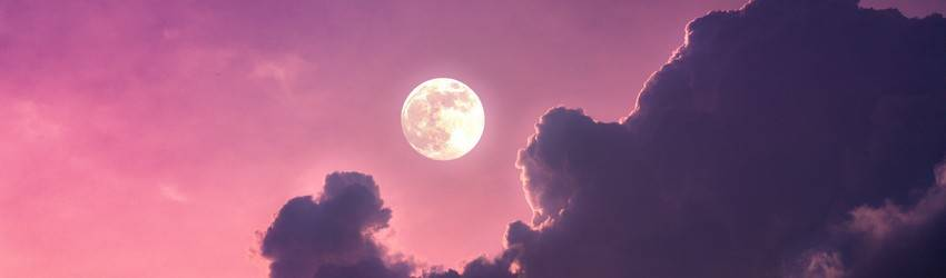 A Full Moon on a purple sky with dark purple clouds floating beneath the Moon.