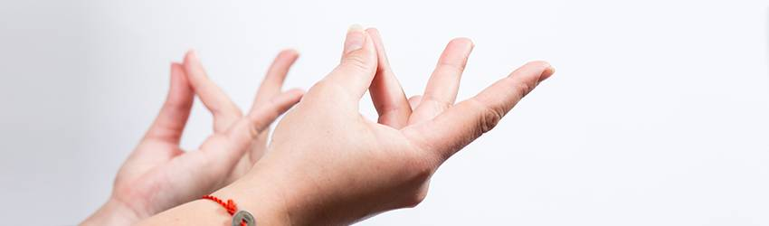 Person holding two hands out to the right upper side of the frame and connecting their fingers together.