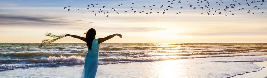 Woman standing on a beach pretending to fly with the birds.