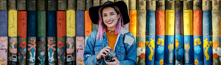 A woman wearing bright colors and a floppy hat. She is representative of an Aquarius woman.