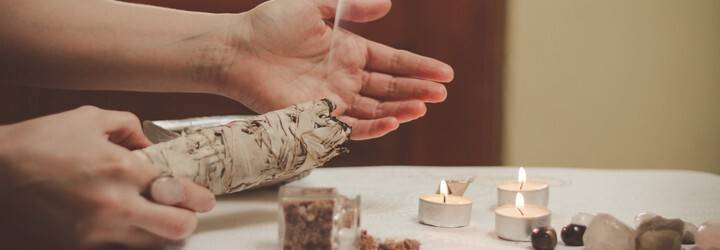 A person lights sage over their New Moon altar.
