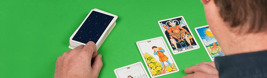 A person is doing a new tarot spread on a green table.