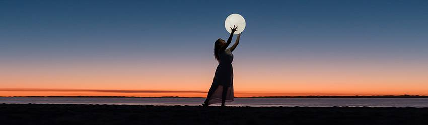 A woman holds a circle that represents the Moon in front of a dark sky.