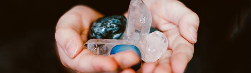 A person holds crystals out in front of them.