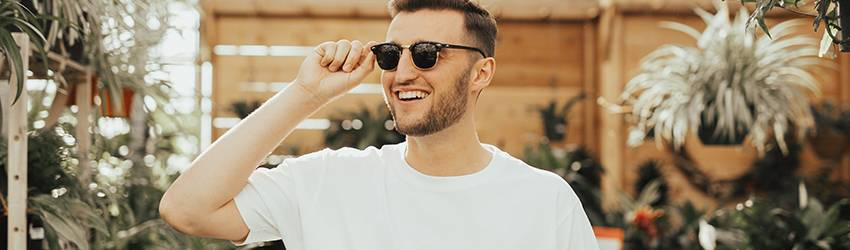 A Sagittarius man stands in a greenhouse with his sunglasses on. He is laughing at something off camera.