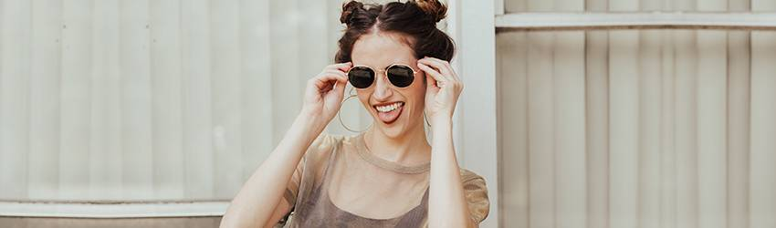 A Sagittarius woman stands in front of a wall making a funny face and raising her sunglasses.