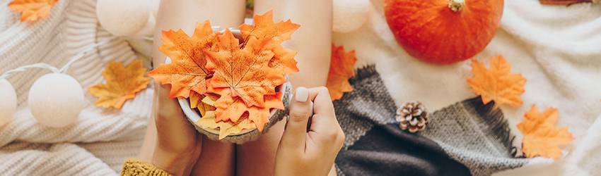 An woman holds an autumn mug on her knees while surrounded by leaves and pumpkins.