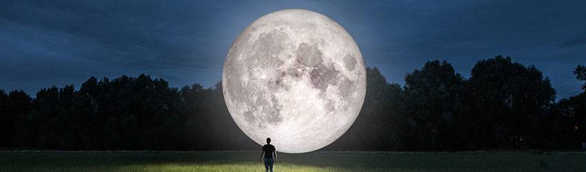 A man stands in front of a large Full Moon.