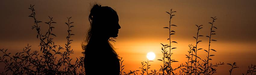A young woman sits in a field in front of a setting sun.