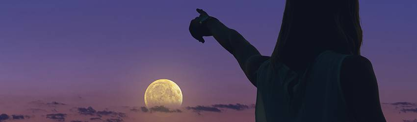 Silhouetted woman pointing at the moon.