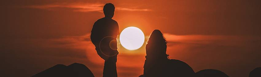 Two people sit in front of a setting sun. The sky is a dark orange and they are silhouetted.