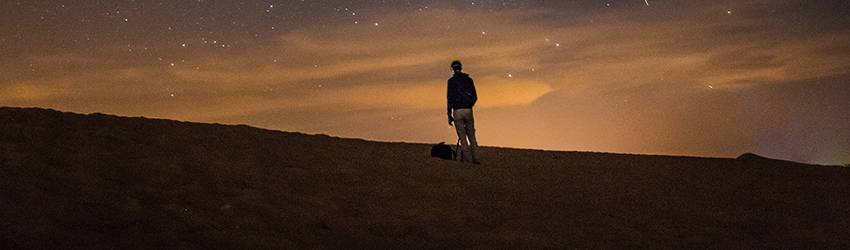 A silhouette on a starry background. The sky is dark blue and orange.