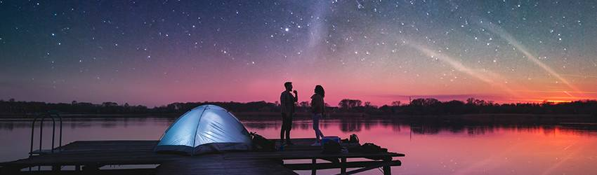 Two people watching the stars while sitting next to their tent.