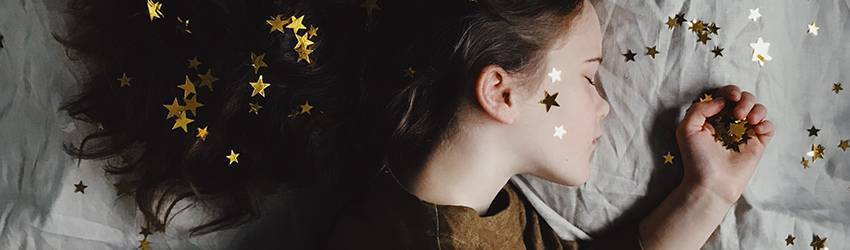A girl sleeping while covered in golden stars.