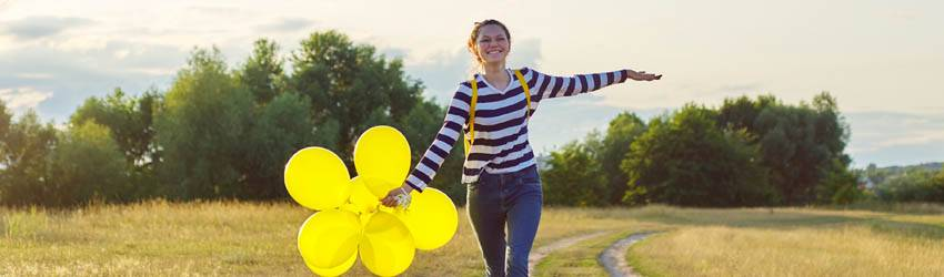 A Leo woman running through a field holding yellow balloons pretending to be an airplane, signifying her confidence soaring.