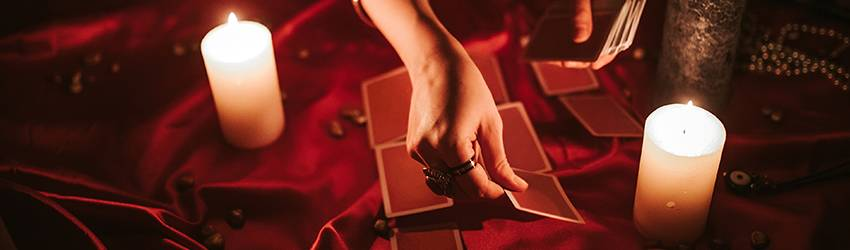 A person is setting out red Tarot cards into a spread on a red table covered in candles.