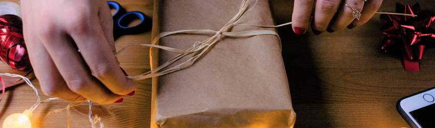 Person wrapping a present with brown paper.