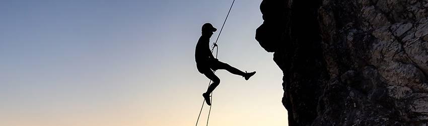 A rock climber propels down a mountain over a beautiful ocean view.