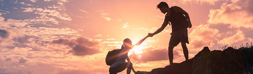 Two people are climbing a mountain. One extends their hand to help the other as the sunrise shadows them.