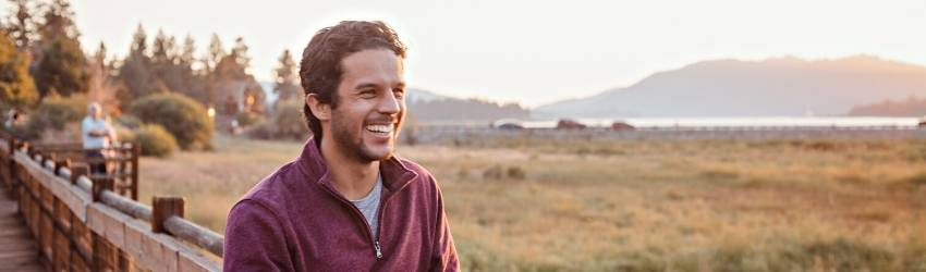 A happy man wearing a sweater is leaning against a fence next to a pleasant field.