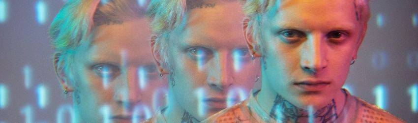 A man with blonde hair faces the camera. The photograph effects make him appear as if he is there 3 times. There are white and blue numbers floating around him and in the background.