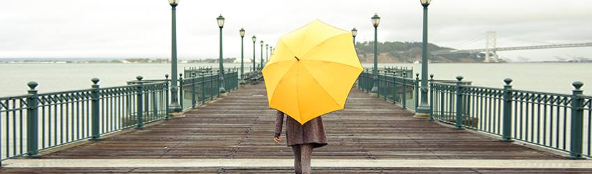 A person walking down a boardwalk with a yellow umbrella.