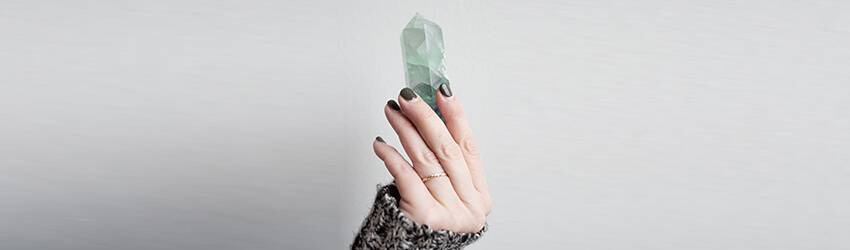 A Pisces woman holding a crystal up against a white wall.