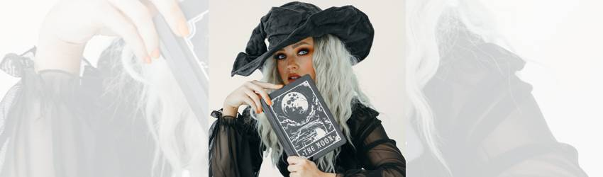 A woman with silver hair wears a witchy hat and holds up a book called