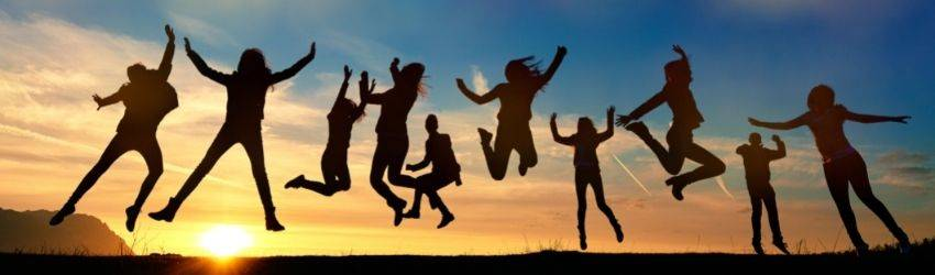 A group of people silhouetted jump in the air at sunset. The sky is brilliant colors of yellow, blue, and orange. They appear to be jumping for joy.