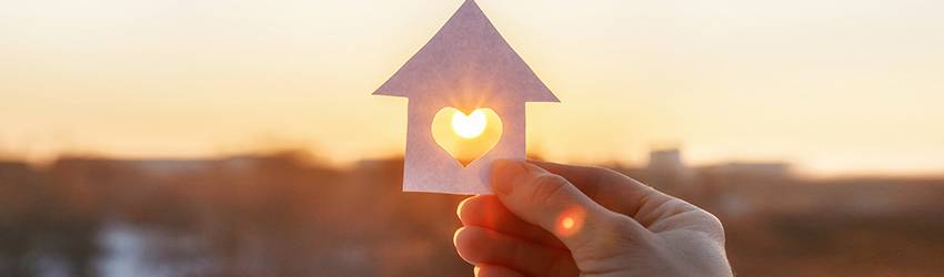 A person holding a paper cut out of a house with a heart in the middle. They are letting the sun through the center.