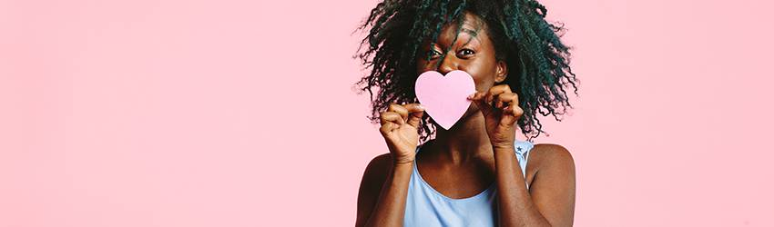 A Black woman holds a pink heart in front of her mouth. She is standing in front of a pink background.
