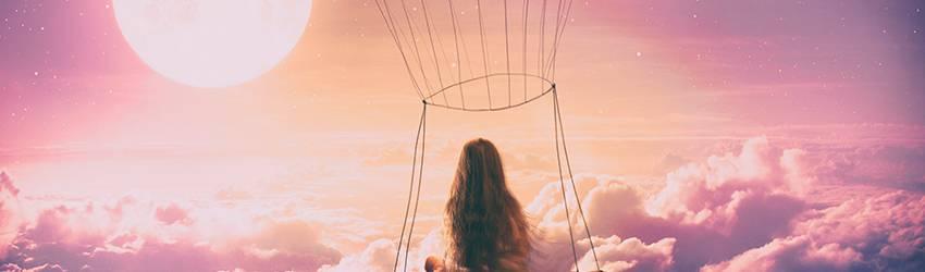Woman in a hot air balloon heading towards a full moon.
