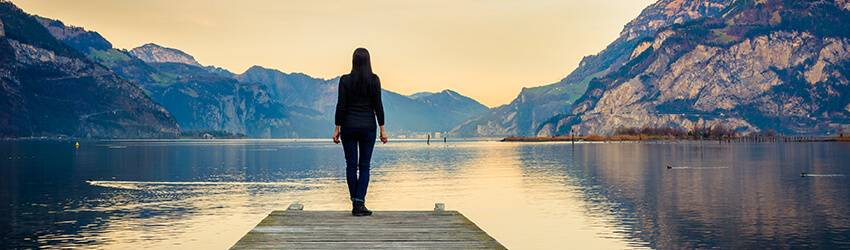 A Pisces stands, looking out at a lake, thinking about life.