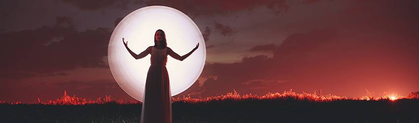 A woman stands in front of a Full Moon in a red sky.